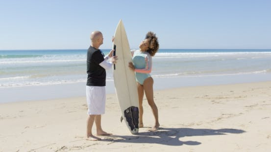 Thumbnail for Male and Female with Surfboard on Beach