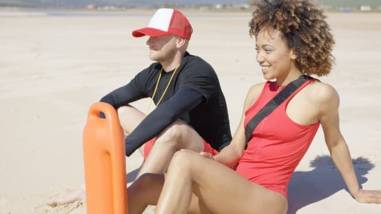 Thumbnail for Smiling Lifeguards Sitting on Beach