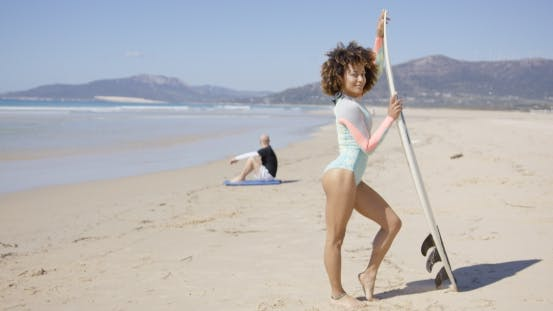 Female Posing with Surfboard on Beach