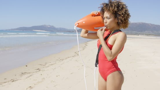 Lifeguard Blowing a Whistle Holding Rescue Float