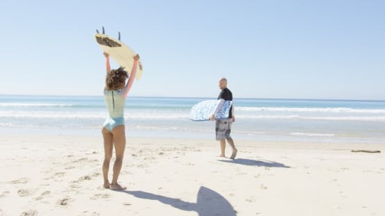 People with Surfboards on Beach