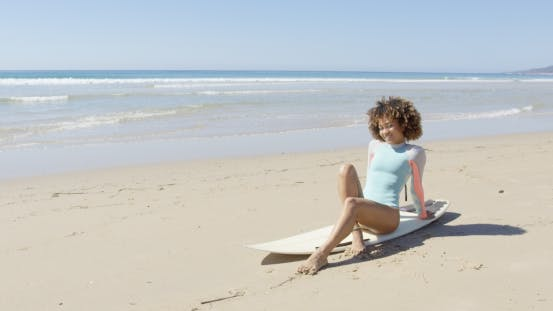 Thumbnail for Young Woman Sitting on a Surfboard