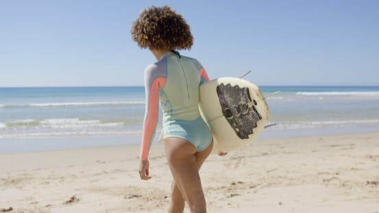 Thumbnail for Female Walking Into Sea To Surf