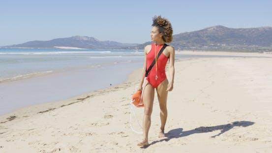 Thumbnail for Female Lifeguard Walking Along Beach