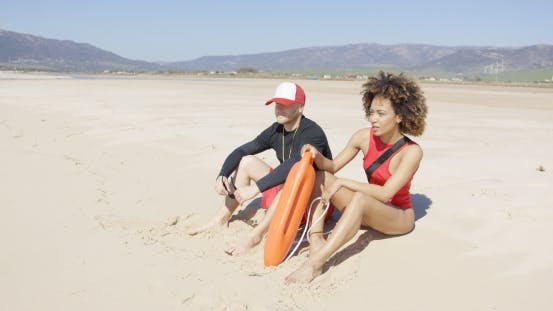 Thumbnail for Female and Male Lifeguards Patrolling Beach