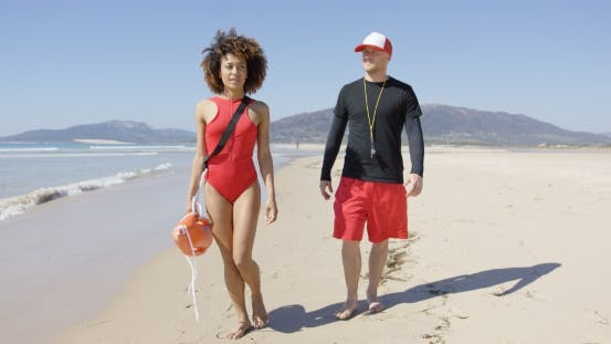 Thumbnail for Female and Male Lifeguards Walking Along Beach
