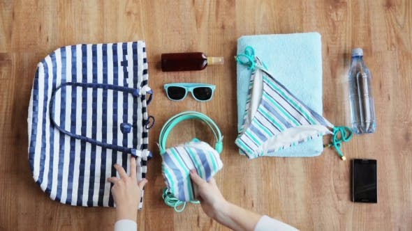 Hands Packing Beach Accessories To Bag 20