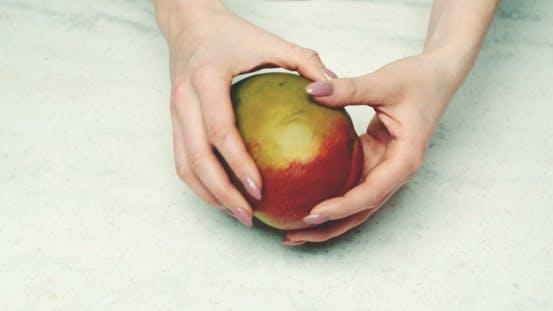 Thumbnail for Woman Examining Fresh Mango At Counter
