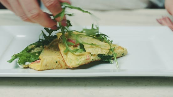 Thumbnail for Woman Garnishing Omelet With Arugula In Plate