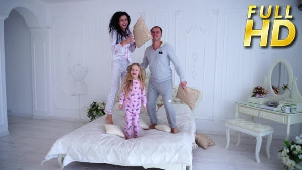 Thumbnail for Portrait of Family Jumping on Bed Looking at