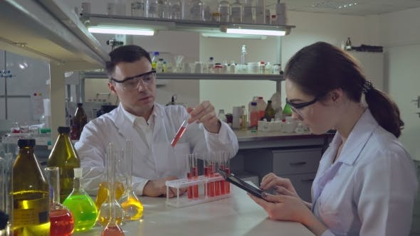 Thumbnail for Chemist Engineer Holding Test Tube with Liquid Talking with Student.