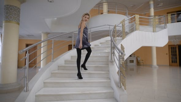 Thumbnail for A Young Girl, Dressed in a Short Suede Dress Up the Stairs, Inviting Us Along. She Turns Back