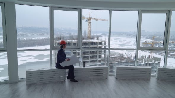 Thumbnail for Man Looking on the Construction Site Through the Window.