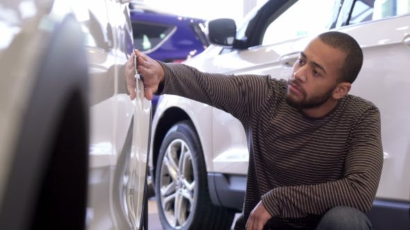Man Touches Car Wing at the Dealership