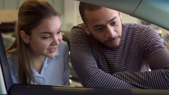 Thumbnail for Couple Looks Inside the Car at the Dealership