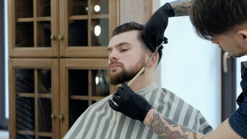 Master Cuts Hair and Beard in the Barber Shop. Cut a Beard with Scissors