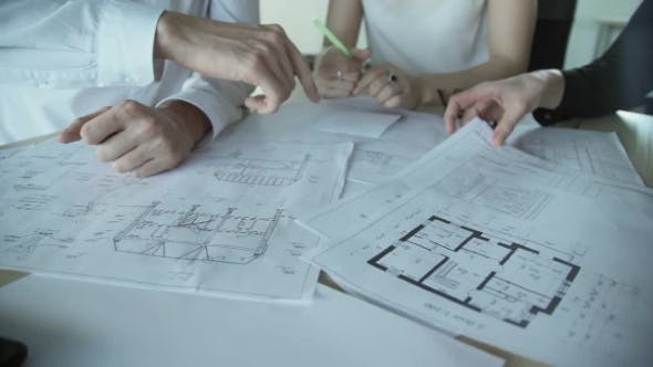 Thumbnail for Hands of Three Workers Discussing Building Drawings in Office