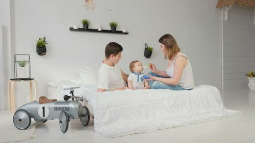 Young Parents Feed Baby on a White Room. Happy Family.