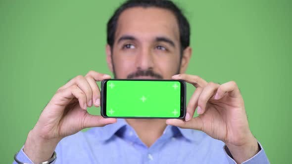 Thumbnail for Young Happy Bearded Indian Businessman Thinking While Showing Phone