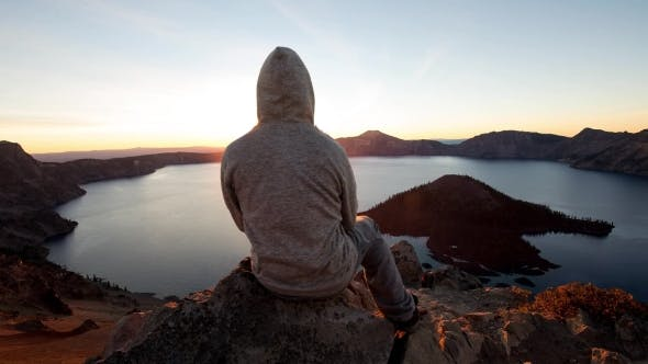 Thumbnail for 2.5D Parallax Video Hooded Man Sitting on Edge of Rock Cliff Watching Sunrise Above Crater Lake