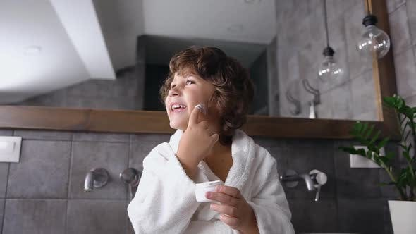 Cover Image for Little Boy in white Robe Sitting Near Bathroom Mirror and Playing with Skin Care Cream