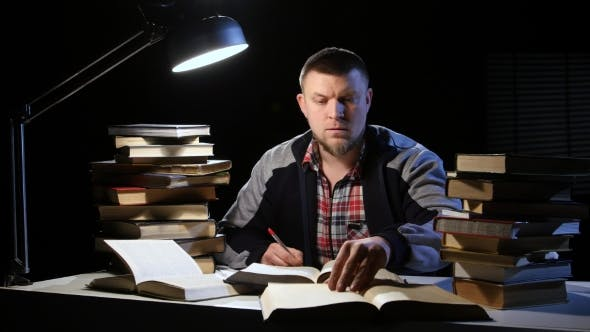 Thumbnail for Man Reading a Book and Writes in a Notebook. Black Background