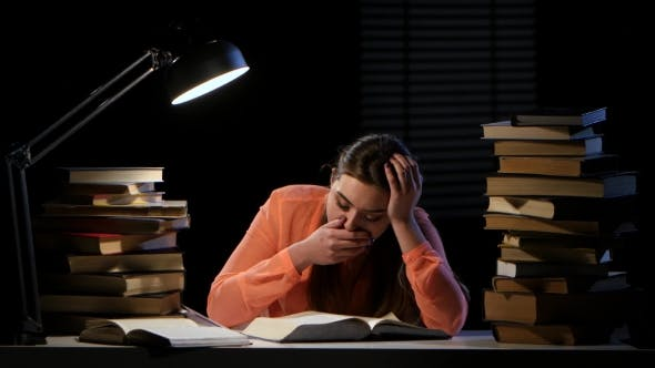 Thumbnail for Girl Leafing Through a Book Yawns and Falls Asleep. Black Background
