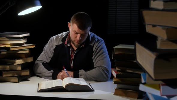 Guy in the Lamplight Records Information on Paper and Crumples It. Black Background