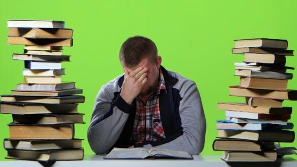 Thumbnail for Man Leafing Through a Textbook, It Suffers From Headaches. Green Screen