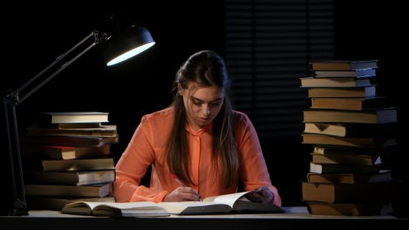 Thumbnail for Girl Reads and Writes Information in a Notebook. Black Background