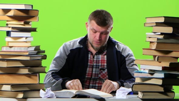 Thumbnail for Man Sitting at His Desk Writes His Notebook Information. Green Screen