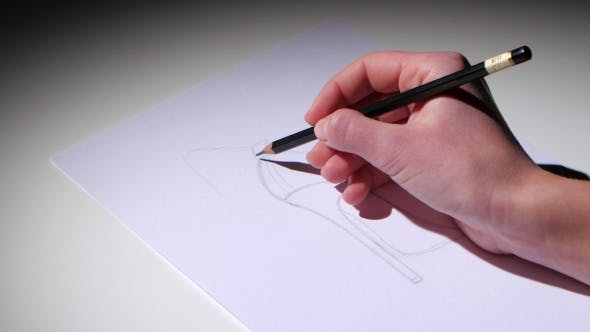Cover Image for Girl Sits at the Table and Draws a Pencil Sketch of the Shoe.