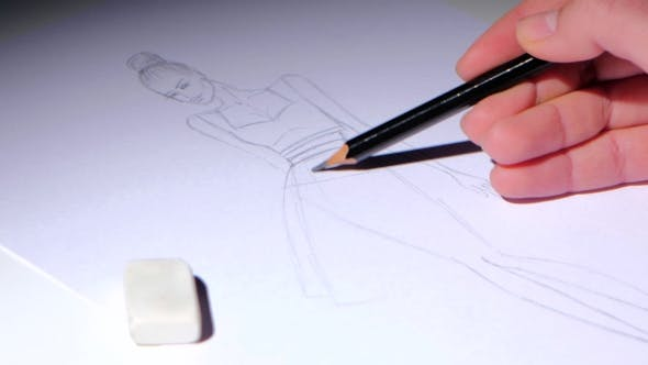 Thumbnail for Designer Creates Fashion Dress Sketch, Sitting at a White Table.
