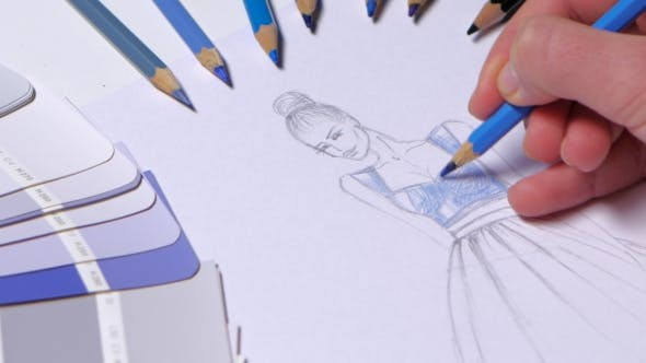 Cover Image for Designer Dress Decorates a Sketch in Blue, on a Table Cloth Samples Lie.
