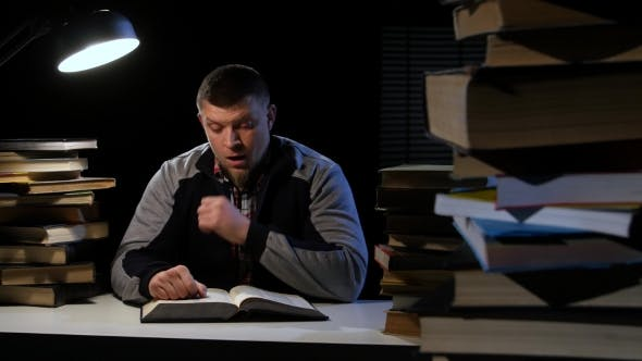 Thumbnail for Man Leafing Through the Book, He Is Sleepy and Tired. Black Background