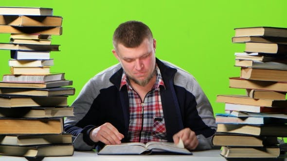 Thumbnail for Man Sitting at Table with Books and Reading an Interesting Chapter. Green Screen