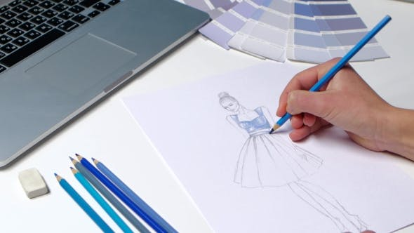 Thumbnail for Designer with a Pencil Sketch Decorates Dresses in Blue.