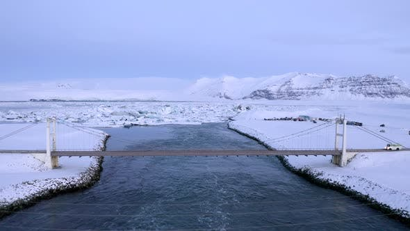 Thumbnail for Flying Over Bridge with Car Driving Over Towards Snowy Ice Floes on Iceland Lake Winter