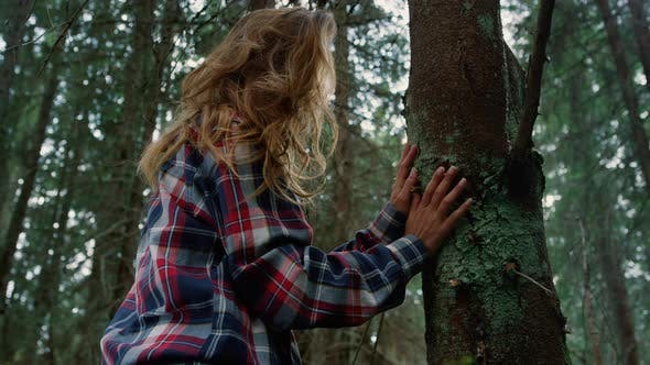 Woman Touching Tree Trunk with Hands in Forest