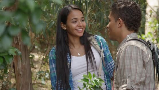 Cute Hispanic girl talking to boyfriend outdoors