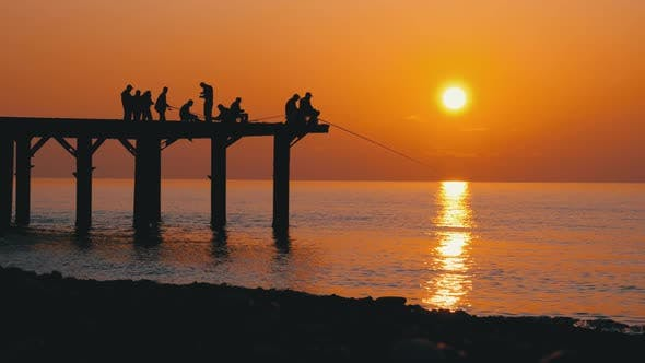 Thumbnail for Silhouettes of Fishermen with Fishing Rods at Sea Sunset Sitting on the Pier. Slow Motion