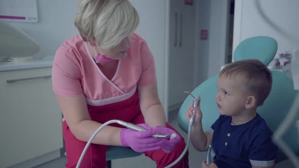 Thumbnail for Dentist in Medical Mask and Gloves Ready To Checking Tooths of Little Carefree Boy Sitting