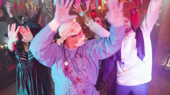 Thumbnail for Man in Evil Doctor Costume Dancing in the Middle of a Group of Friends Celebrating Halloween