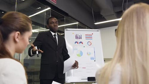 African American Businessman Explaining Project Graph During Flip Chart Presentation for Considerate