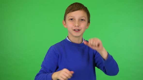 Thumbnail for A Young Cute Boy Dances and Smiles at the Camera - Green Screen Studio