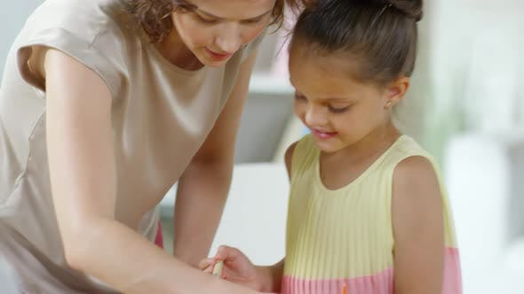 Cover Image for Female Teacher Helping Little Girl to Make Paper Craft