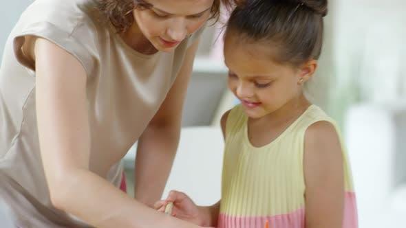 Thumbnail for Female Teacher Helping Little Girl to Make Paper Craft