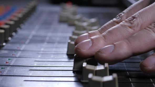 Thumbnail for Faders Sliding Under Fingers of Record Producer