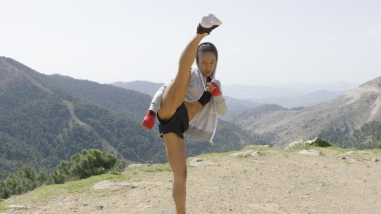 Young Female Kickboxer in Mountains