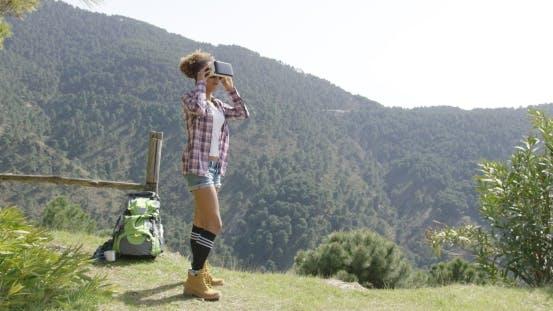Cover Image for Junge Frau in VR Brille unter den Bergen